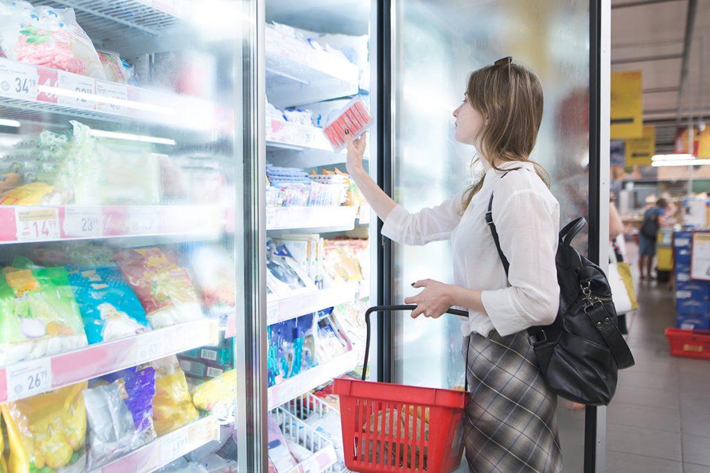 Frau kauft Tiefkühlprodukte im Supermarkt.