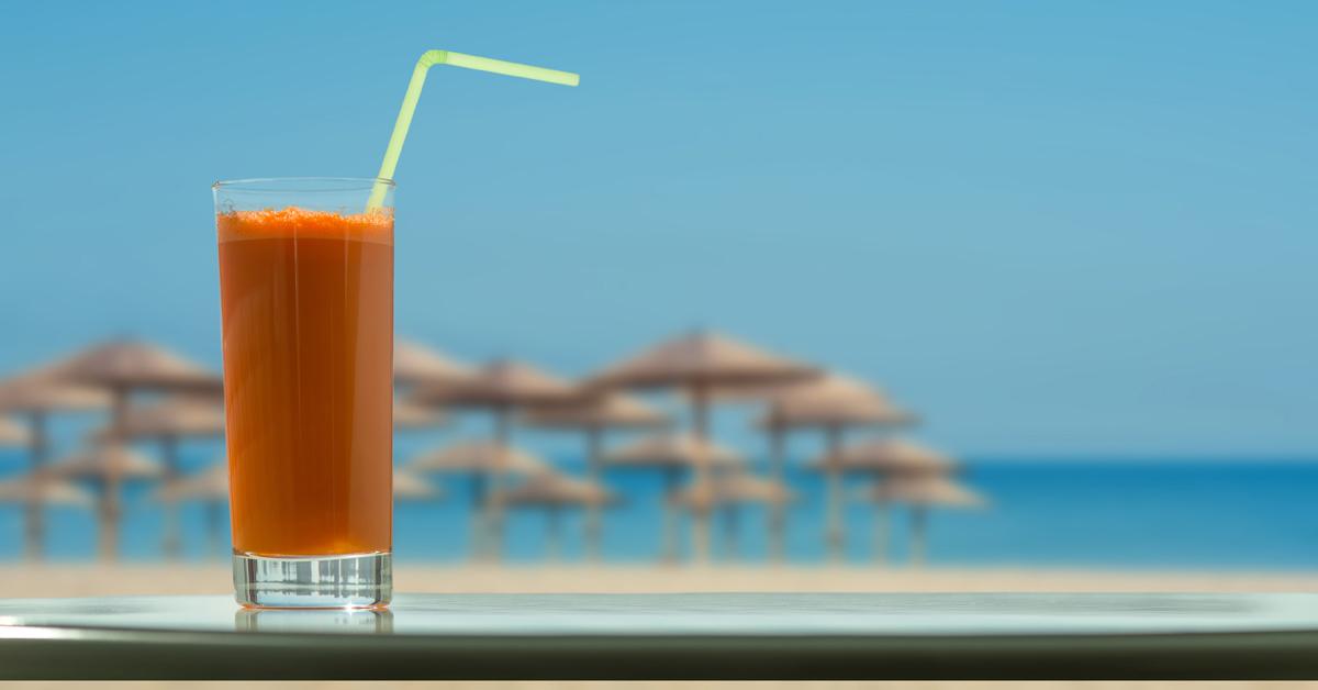 Ein Glas Karottensaft am Strand