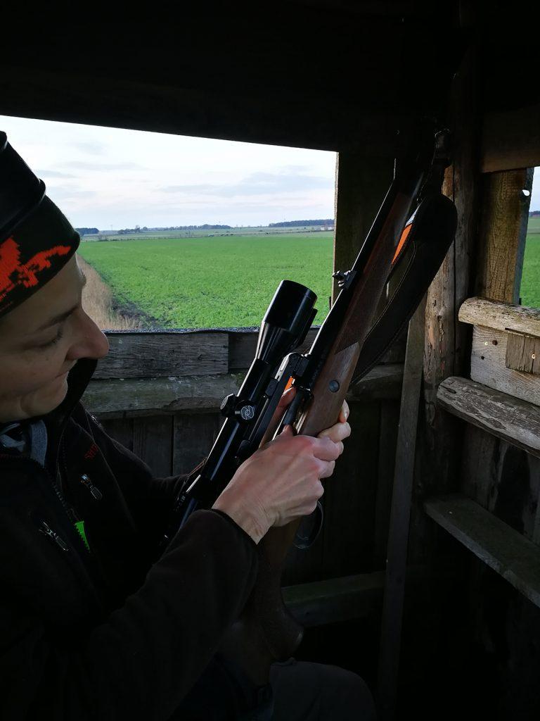 Jägerin mit Gewehr auf dem Hochsitz