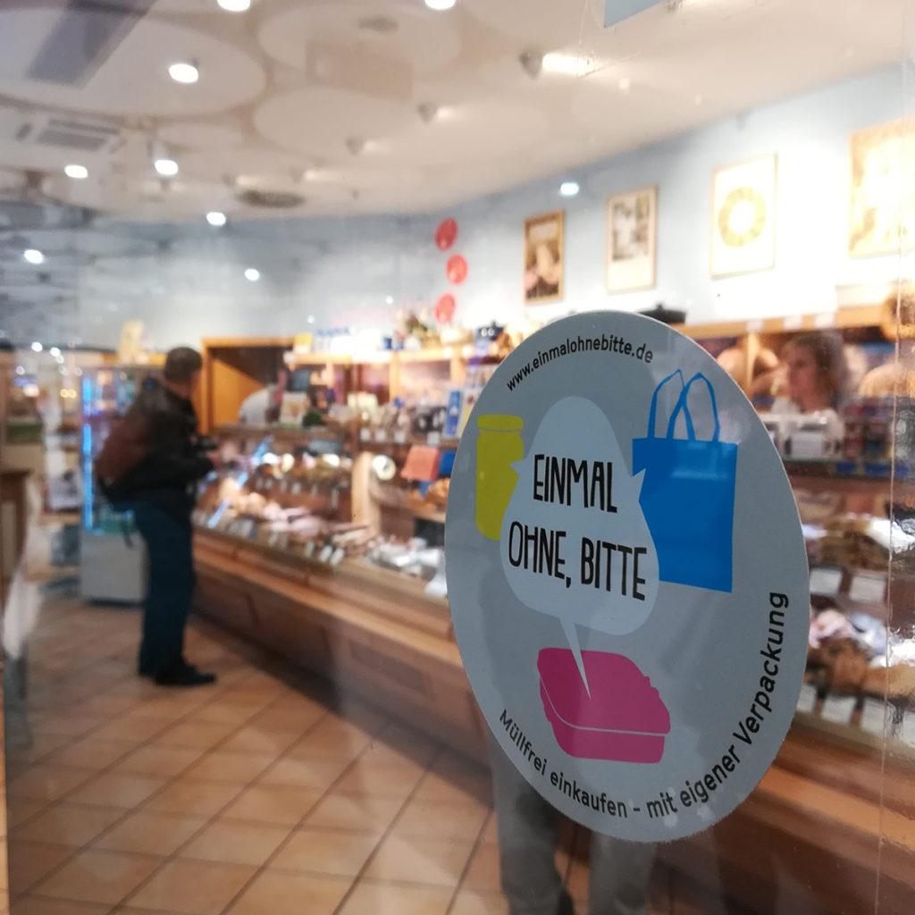 """Sticker der NGO-Kampagne """"Einmal ohne, bitte!"""" an einem Geschäft."""