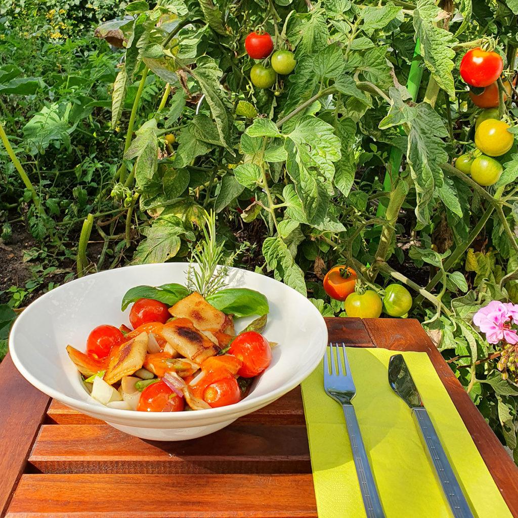 Gebratene Ravioli mit Gemüse und Kirschtomaten.